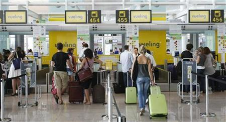 tourists checking in at the airport. Average room prices across the globe fell 17 percent in the six months to June compared to the same 2008 period. Reuters photo.