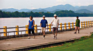 Tourists enjoy a leisurely walk on the embankment built to contain the Mekong River.